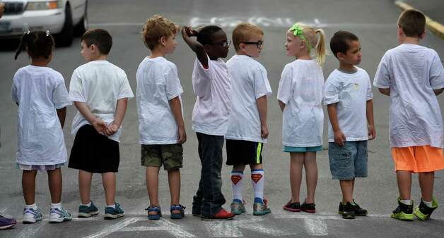 Kindergartners and first graders stand on the starting line of the Color-a-thon,  running race as part of the final days of school Tuesday morning, June 23, 2015, at School 16 in Troy, N.Y.  The event was  fundraiser for the PTA.   (Skip Dickstein/Times Union) Photo: SKIP DICKSTEIN / 00032326A