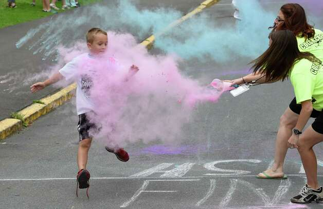 A student gets a blast of color as he runs through the pink dust during the Color-a-thon, running race as part of the final days of school Tuesday morning, June 23, 2015, at School 16 in Troy, N.Y.  The event was  fundraiser for the PTA.   (Skip Dickstein/Times Union) Photo: SKIP DICKSTEIN / 00032326A