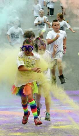 A student gets a blast of color as she runs through the pink dust during the Color-a-thon, running race as part of the final days of school Tuesday morning, June 23, 2015, at School 16 in Troy, N.Y.  The event was  fundraiser for the PTA.   (Skip Dickstein/Times Union) Photo: SKIP DICKSTEIN / 00032326A