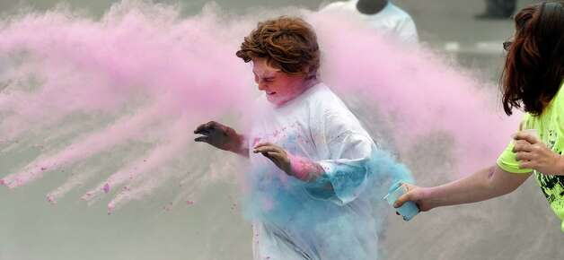 Sydney Bloomfield sees nothing but pink as she passes the finish line in the Color-a-thon, running race as part of the final days of school Tuesday morning, June 23, 2015, at School 16 in Troy, N.Y.  The event was  fundraiser for the PTA.   (Skip Dickstein/Times Union) Photo: SKIP DICKSTEIN / 00032326A
