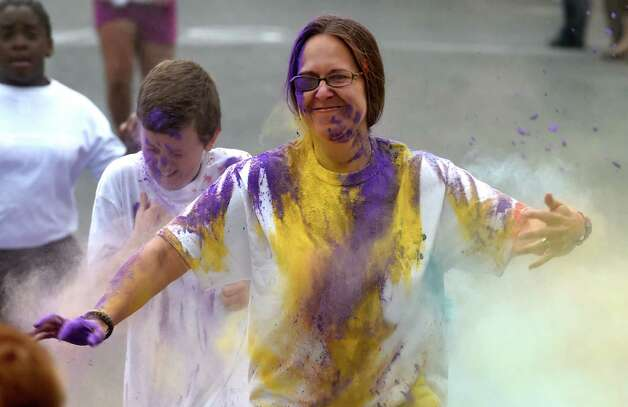 Mom Staci Lansley gets a gets a blast of color as she runs through the pink dust during the Color-a-thon, running race as part of the final days of school Tuesday morning, June 23, 2015, at School 16 in Troy, N.Y.  The event was  fundraiser for the PTA.   (Skip Dickstein/Times Union) Photo: SKIP DICKSTEIN / 00032326A