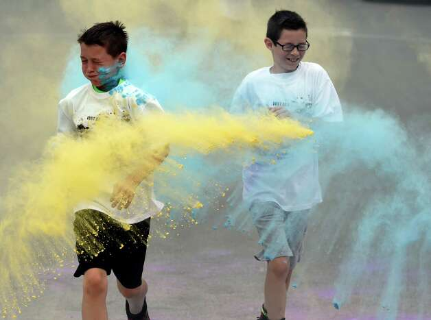 Colin McBride, left and Owen Brown try to avoid the blasŽ of corn starch during the Color-a-thon, running race as part of the final days of school Tuesday morning, June 23, 2015, at School 16 in Troy, N.Y.  The event was  fundraiser for the PTA.   (Skip Dickstein/Times Union) Photo: SKIP DICKSTEIN / 00032326A