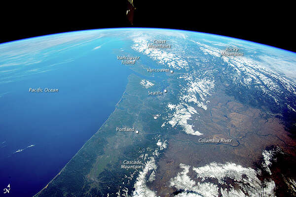 NASA's great caption (for a larger view click on the same photo at bottom of story): This panoramic photograph was taken by an astronaut looking north from the International Space Station. The snow-covered Cascade Range of the U.S. northwest in the foreground gives way to the Rocky Mountains and Coast Mountains in Canada, with Vancouver Island just offshore.   Several active volcanoes—Mount St. Helens, Mount Rainier and Mount Hood—dot the Cascades. One of the space station's solar arrays points into the view on the upper left. Short-lens panoramic views often reveal environmental patterns. The cloud bands of an approaching winter storm (upper left) signal a bout of approaching rain to what is one of the wettest parts of North America. Greener, forested landscapes are evidence of the wet climate experienced by people who live near the coast and on the seaward slopes of the mountains.   By contrast, the tan colors of the dry Columbia Basin (lower right) show the rain shadow effect of the Cascades in preventing rain-bearing air masses from reaching the basin. In the foreground, the Columbia River drains the basin, cuts directly through the Cascades at Columbia River Gorge, and then flows into the Pacific Ocean.   Cities typically appear as dull gray zones, but astronauts learn to detect these sometimes difficult targets. In this image, Portland, the Seattle-Tacoma metropolis, and Vancouver are all visible. Mount Rainier lies immediately southeast of Seattle about 65 kilometers (40 miles) away.