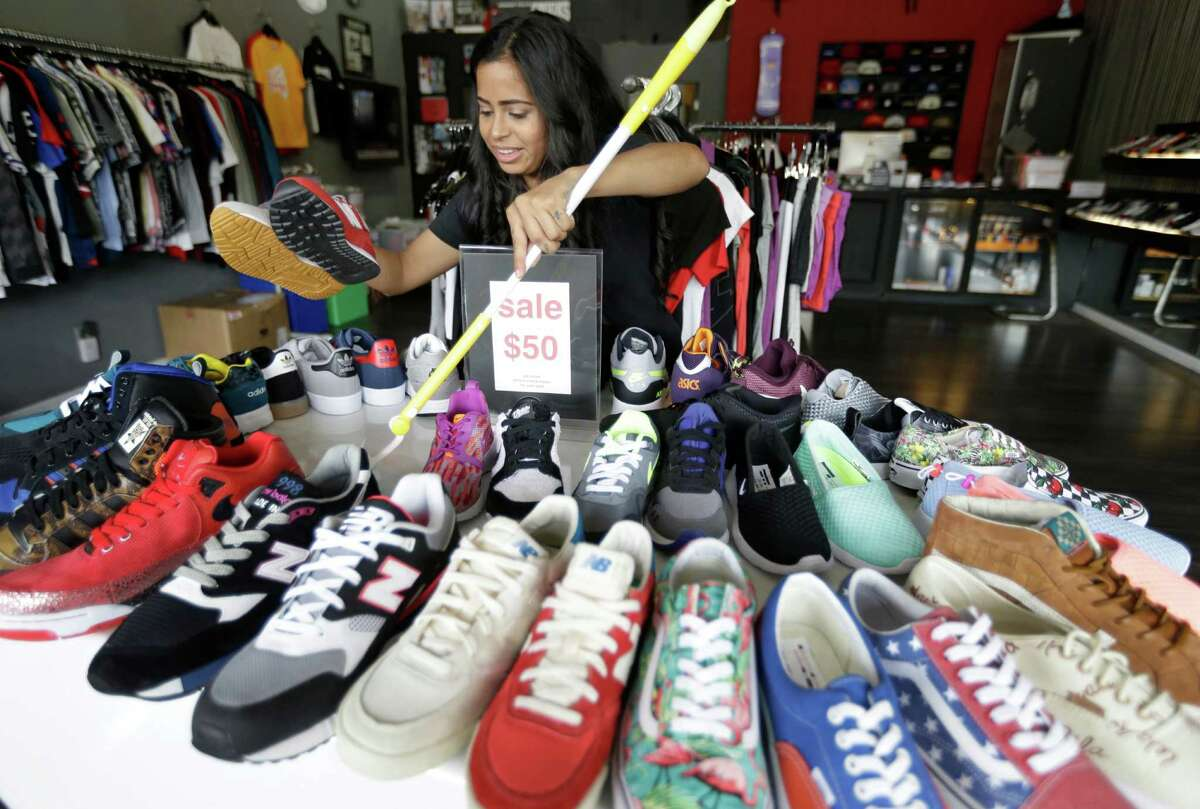 Nathalie Ortez cleans a shoe display at Premium Goods, 2416 Times Boulevard, Tuesday, June 23, 2015, in Houston. ( Melissa Phillip / Houston Chronicle )