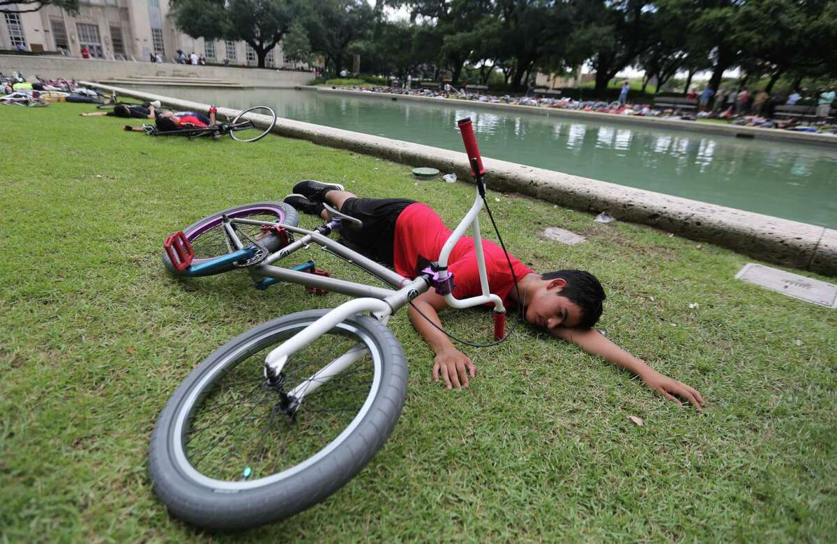 Marcus Aguayo sets down his bicycle in a silent protest for 4 minutes outside City Hall to remind motorist to share the road with cyclist on Tuesday, June 23, 2015, in Houston. In the past three weeks, there have been 4 bicycle related fatalities in Houston. Three of those deaths were at the hands of someone driving a car. The fourth one was cause by debris leading to a crash on the Elysian Bridge.