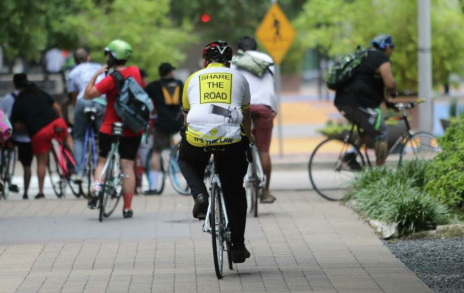 "A cyclist wears a ""Share The Road"" shirt to a silent protest outside City Hall to remind city council to enforce the 3 feet rule for motorist on Tuesday, June 23, 2015, in Houston. In the past three weeks, there have been 4 bicycle related fatalities in Houston. Three of those deaths were at the hands of someone driving a car. The fourth one was cause by debris leading to a crash on the Elysian Bridge. Photo: Mayra Beltran, Houston Chronicle / © 2015 Houston Chronicle"
