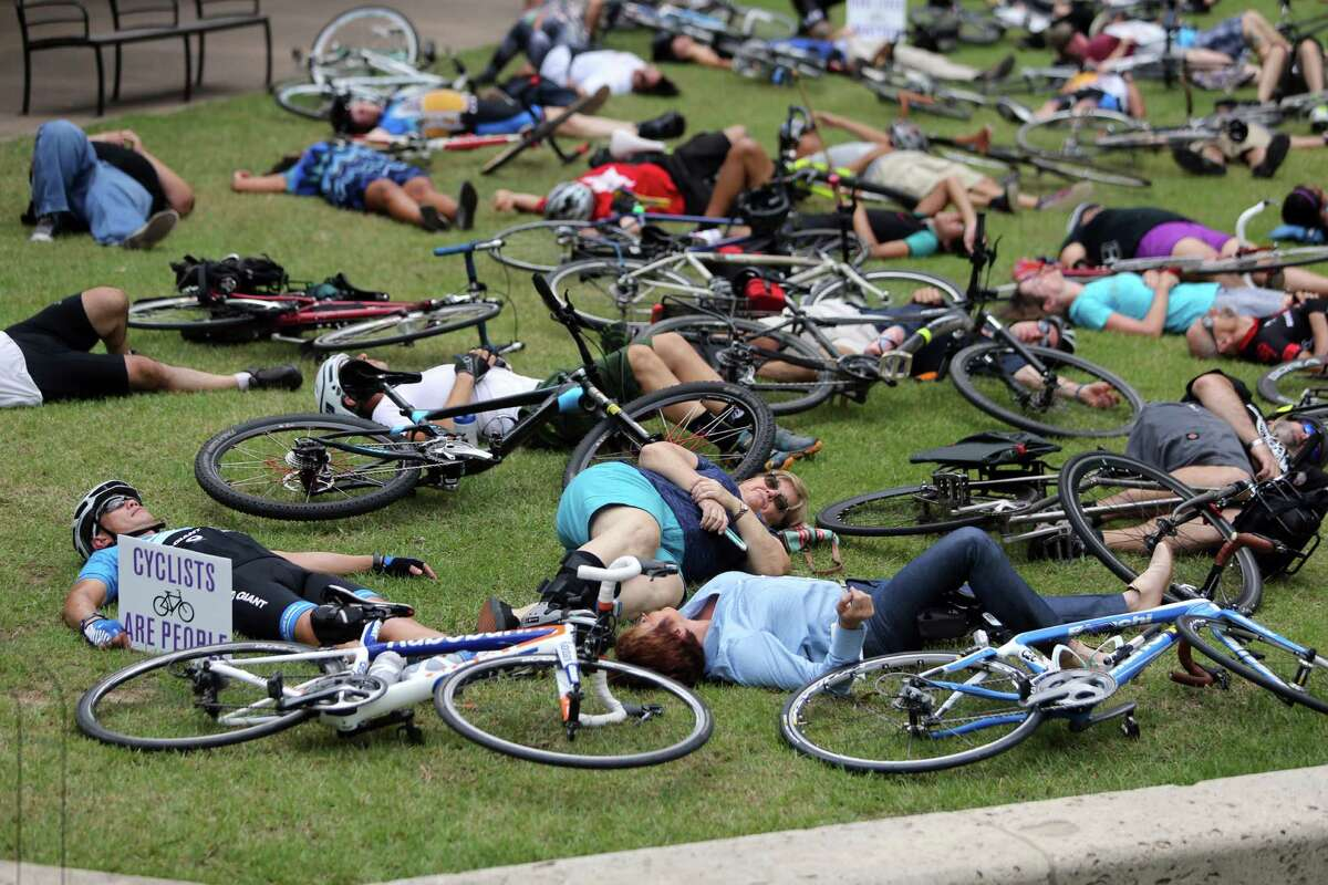 Cyclist lie down with their bicycles in a silent protest for 4 minutes outside City Hall on Tuesday, June 23, 2015, in Houston. In the past three weeks, there have been 4 bicycle related fatalities in Houston. Three of those deaths were at the hands of someone driving a car. The fourth one was cause by debris leading to a crash on the Elysian Bridge.