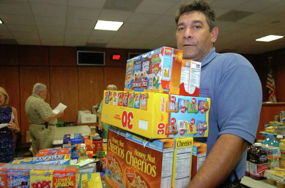 Louis Borselio, of Riverside, who works in the Greenwich parking services department, donated food during to the Salvation Army's Greenwich Town Hall employee food drive in 2010. This year's food drive is set for Thursday. Photo: Helen Neafsey / Greenwich Time / Greenwich Time
