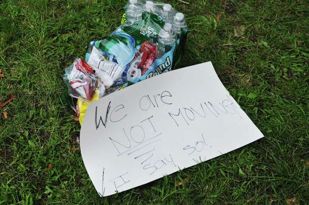 Bottles of water, bags of snacks and a sign are seen on the ground in Academy Park on Tuesday, June 23, 2015, in Albany, N.Y., where New York City tenants and advocates slept overnight. The group is calling on the governor and legislators to strengthen rent laws and end deregulation and eliminate the loopholes that have allowed rents to skyrocket.    (Paul Buckowski / Times Union) Photo: PAUL BUCKOWSKI / 00032370A