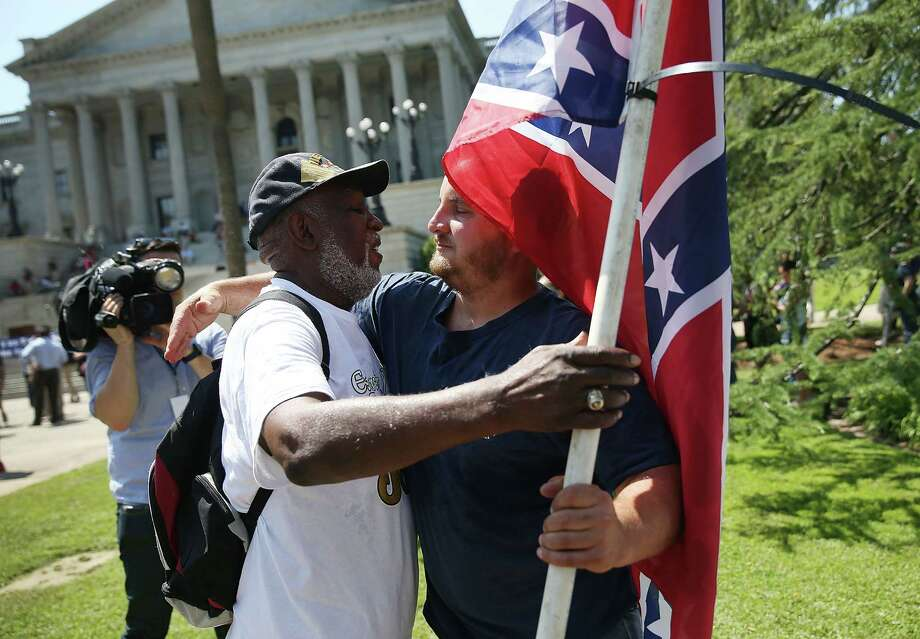 Ernest Branch, left, hugs a Confederate flag supporter in front of the South Carolina Capitol.  Branch is against flying the flag on state grounds. Photo: Joe Raedle, Staff / 2015 Getty Images