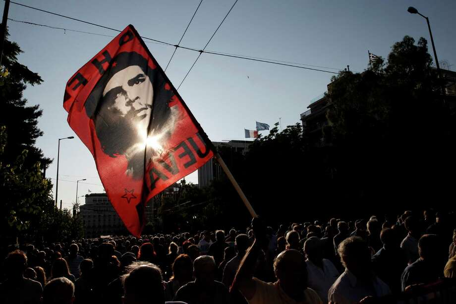 A Greek pensioner holds a flag bearing an image of Argentine revolutionary Che Guevara during an  anti-austerity protest Tuesday in Athens. Photo: Petros Giannakouris, STF / AP