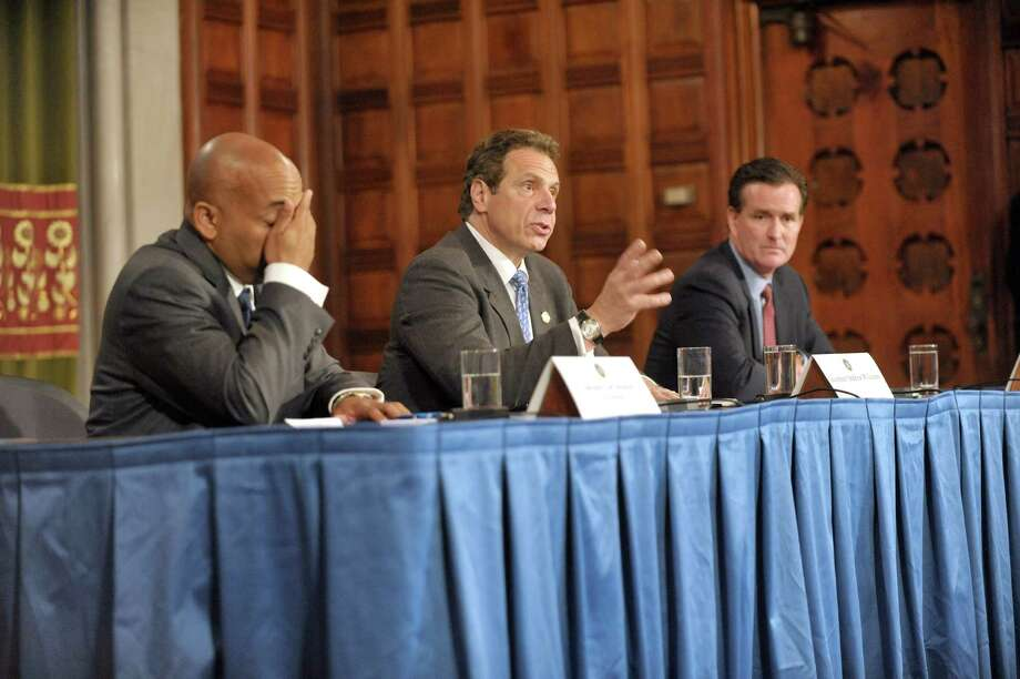 New York State Assembly Leader Carl Heastie, left, wipes his face as he and Governor Andrew Cuomo, center, and New York Senate Majority Leader John Flanagan take part in a press conference at the Capitol where the three announced that they have reached a framework deal on Tuesday, June 23, 2015, in Albany, N.Y.   (Paul Buckowski / Times Union)      (Paul Buckowski / Times Union) Photo: PAUL BUCKOWSKI / 00032366A