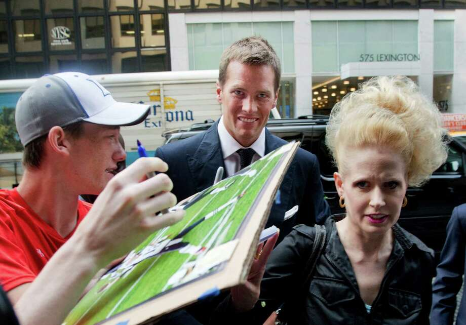 A fan intercepts Patriots quarterback Tom Brady as he arrives for his appeal hearing with NFL Players Association attorney Heather McPhee, right. Photo: Mark Lennihan, STF / AP