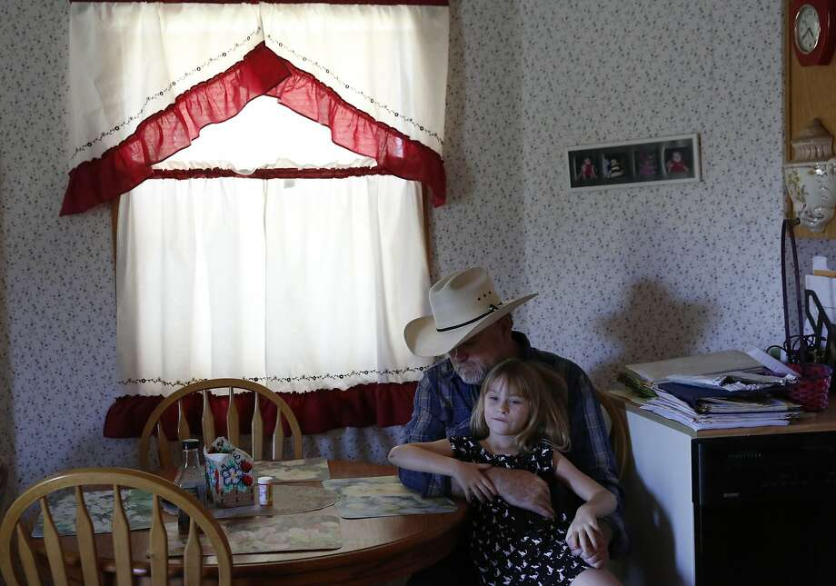 """Dennis Baker, 53, hangs out with his granddaughter Kaylie Baker, 6, before a delayed Father's Day dinner for him June 23, 2015 at Baker's home, situated on his farmland in Tracy, Calif. Baker farms 40 acres of hay and says that if his senior water rights are cut off, he will lose his crop, which he thinks could survive with only two more irrigations. Baker's concern is that his """"permanent pasture"""" of reseeding grass will die. The grass has been reseeding itself for over 50 years and if it dies, he will have to replant it, which will cost extra money he won't have if he loses his crop. On Tuesday there was a hearing at the San Joaquin County Superior court between the State Water Board and the Banta-Carbona Irrigation District to decide whether it is legal for the state to stop water diversions to senior water rights holders in the district. Photo: Leah Millis, The Chronicle"""