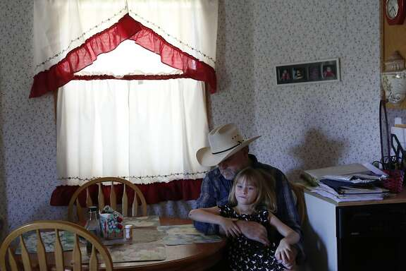 """Dennis Baker, 53, hangs out with his granddaughter Kaylie Baker, 6, before a delayed Father's Day dinner for him June 23, 2015 at Baker's home, situated on his farmland in Tracy, Calif. Baker farms 40 acres of hay and says that if his senior water rights are cut off, he will lose his crop, which he thinks could survive with only two more irrigations. Baker's concern is that his """"permanent pasture"""" of reseeding grass will die. The grass has been reseeding itself for over 50 years and if it dies, he will have to replant it, which will cost extra money he won't have if he loses his crop. On Tuesday there was a hearing at the San Joaquin County Superior court between the State Water Board and the Banta-Carbona Irrigation District to decide whether it is legal for the state to stop water diversions to senior water rights holders in the district."""