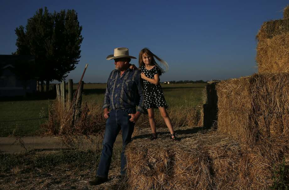 Dennis Baker, 53, stands with his granddaughter Kaylie Baker, 6, next to his first cutting of hay this year outside of his home on June 23. Photo: Leah Millis, The Chronicle