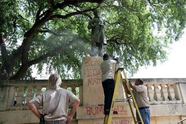 "Sergio Martinez, center, with UT Facilities Services, pressure washes a statue of Jefferson Davis to remove graffiti at the University of Texas campus in Austin, Texas, on Tuesday, June 23, 2015.  Cindy Posey, spokeswoman for campus security at UT, says ""Black lives matter"" was scrawled early Tuesday on the base of the statue to the president of the Confederacy, and also on those for Confederate Gens. Robert E. Lee and Albert Johnston.   (Dborah Cannon/Austin American-Statesman via AP)  AUSTIN CHRONICLE OUT, COMMUNITY IMPACT OUT, INTERNET AND TV MUST CREDIT PHOTOGRAPHER AND STATESMAN.COM, MAGS OUT"