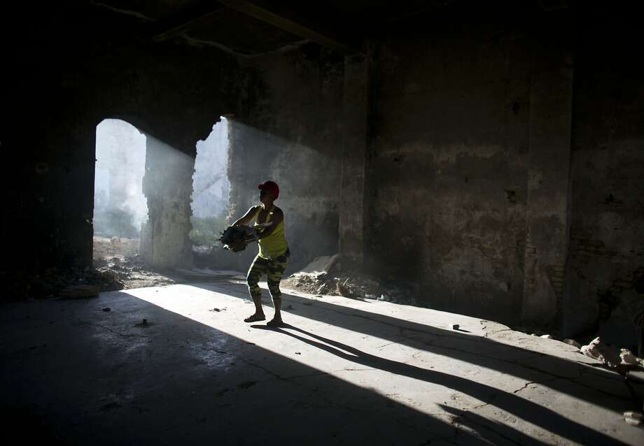A woman removes trash to be burned, as she cleans inside an earthquake damaged building in downtown Port-au-Prince, Haiti, Tuesday, June 23, 2015. Throughout downtown Port-au-Prince, severely earthquake damaged buildings continue to be used by some of the capital's poorest as open-air homes, work spaces, showers, and toilets. Photo: Rebecca Blackwell, Associated Press