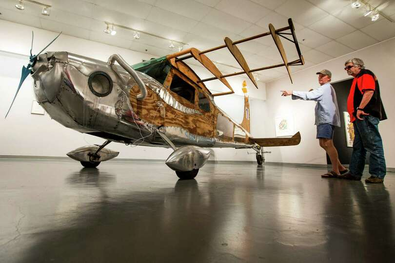 Dion Laurent, left, shows Noah Edmundson his art car, Airplane 1, inside the Art Car Museum. The