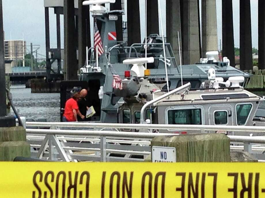 A crew from the U.S. Coast Guard stands on a cutter at the Bridgeport/Port Jefferson ferry dock after a body was recovered in Long Island Sound in a weedy area off Seaside Park in Bridgeport, Conn. on Friday, June 19, 2015. Police Lt. Brian Fitzgerald  said there were no obvious signs of foul play. Employees of the Bridgeport/Port Jefferson Ferry had reported that a passenger may have fallen from a boat late Thursday or early Friday, officials confirmed. They were not yet able to say whether the man whose body was found had been on the ferry. Photo: Frank Juliano / Hearst Connecticut Media / Connecticut Post