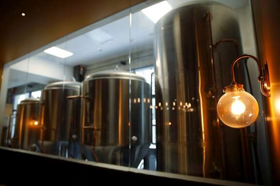 Brewing equipment sits in a room visible through a large window in Dirty Water in San Francisco, California, on Tuesday, June 23, 2015. The bar plans on brewing beer on site.