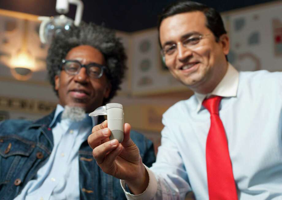 Cedric Campbell, left, opted to use the AcceleDent device after Dr. Vijay Bhagia told him it could cut in half the time he would have to wear braces. Photo: Alysha Beck, Freelance / Houston Chronicle