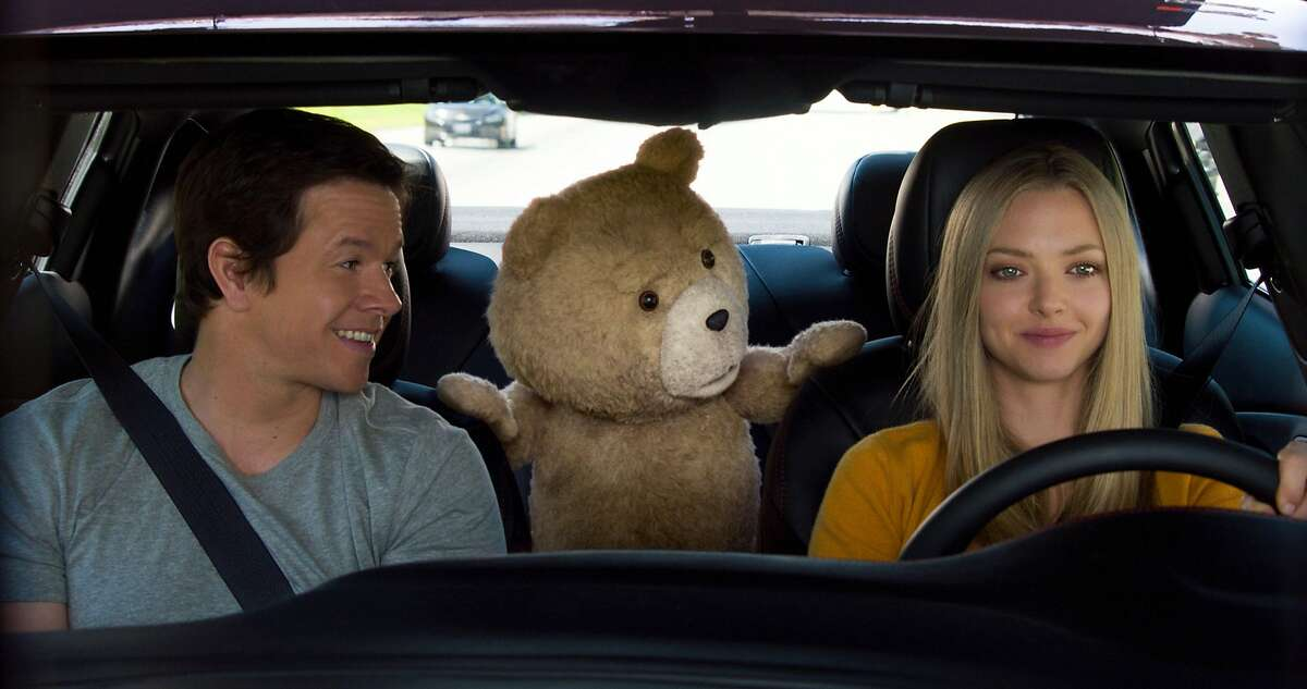 In this image released by Universal Pictures, Mark Wahlberg , from left, the character Ted, voiced by Seth MacFarlane, and Amanda Seyfried appear in a scene from