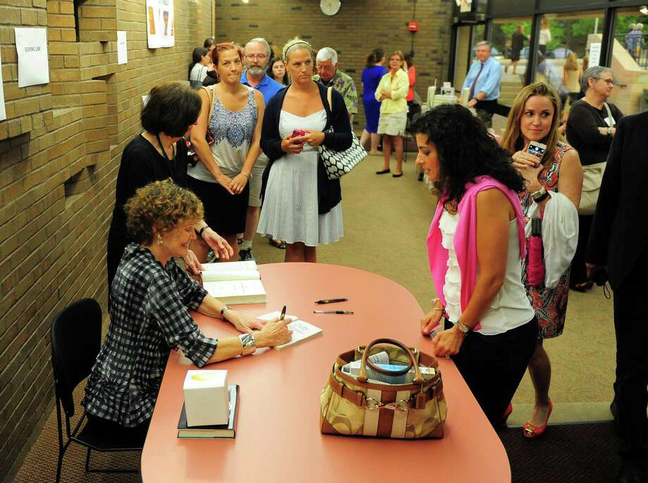 Acclaimed writer Judy Blume autographs her new novel for Gina Mugavero, of Old Greenwich, during a book signing event held at Greenwich Library's Cole Auditorium in Greenwich, Conn., on Tuesday June 23, 2015. Before the book signing, Blume spoke to a packed room about her bestsellers, like Are You There God? It's Me, Margaret, as well as her new novel In the Unlikely Event. Photo: Christian Abraham / Hearst Connecticut Media / Connecticut Post