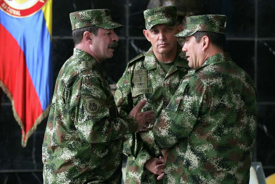 FILE - In this Feb. 18, 2014, file photo, the new Colombian armed forces commander Gen. Juan Pablo Rodriguez, right, talks to newly appointed chief of staff Gen. Javier Florez, left, and army commander Gen. Jaime Lasprilla, center, after a press conference where Defense Minister Juan Carlos Pinzon announced the firing of the fromer armed forces chief Gen. Leonardo Barrero in Bogota, Colombia. Gen. Rodriguez and Gen. Lasprilla are among dozens of senior Colombian army officers implicated in the killing of 3,000 civilians falsely claimed to be rebels a decade ago have risen through the ranks and are escaping punishment for their roles in one of the worst atrocities committed in Latin America, Human Rights Watch said Wednesday, June 23, 2015. (AP Photo/Fernando Vergara, File) Photo: Fernando Vergara, STF / AP