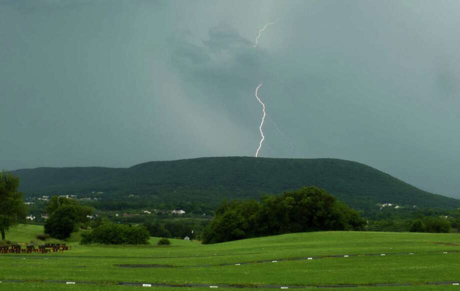 Lightning strikes over Mount Nittany in State College, Pa., as a thunderstorm moves through. Electricity was out Wednesday for tens of thousands of customers across the Northeast. Photo: Nabil K. Mark, MBI / Centre Daily Times