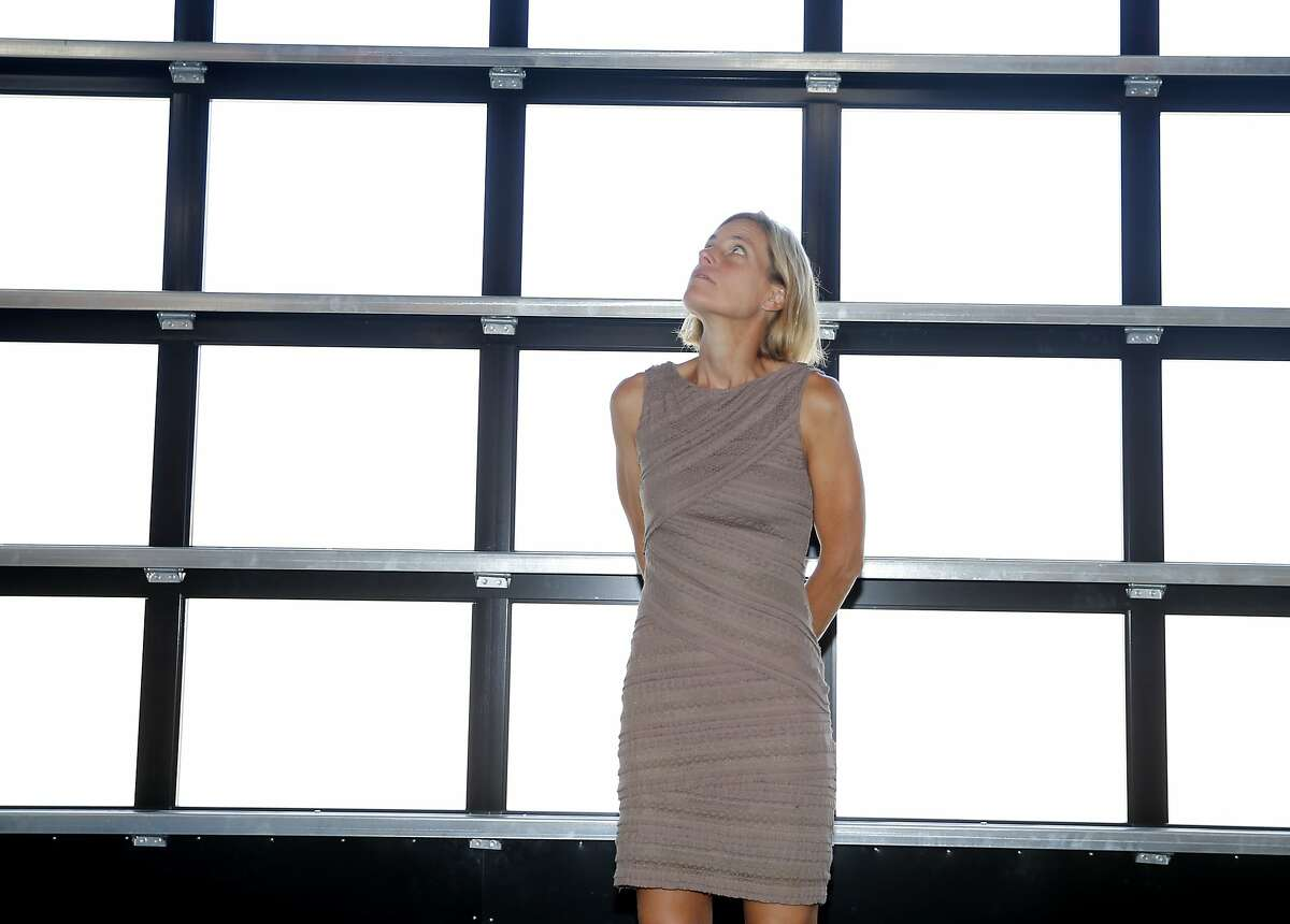 Diane Evans admires the view from the huge glass door at one end of the museum Wednesday June 24, 2015. Diane Evans, the executive director of the new Art Museum of Sonoma County in Santa Rosa, Calif. Currently the museum has a show by noted artist Robt. Williams.