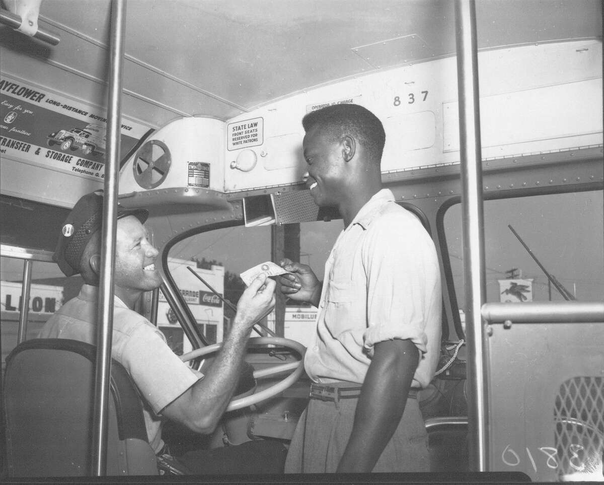 """A bus driver makes change for a rider on a segregated bus in San Antonio in 1949. To the left of the rider's head can be seen a small sign reading """"State law: Front seats reserved for white patrons."""""""