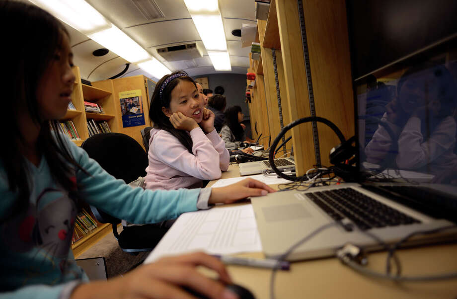 Connie Ma, 10 (center), watches Ashley Liang, 10 (left), look for photos for her storyboard inside the Tech Mobile bus, among the S.F. library's new tech tools, in front of the Visitacion Valley Boys and Girls Club. . Photo: Brandon Chew / Photos By Brandon Chew / The Chronicle / ONLINE_YES