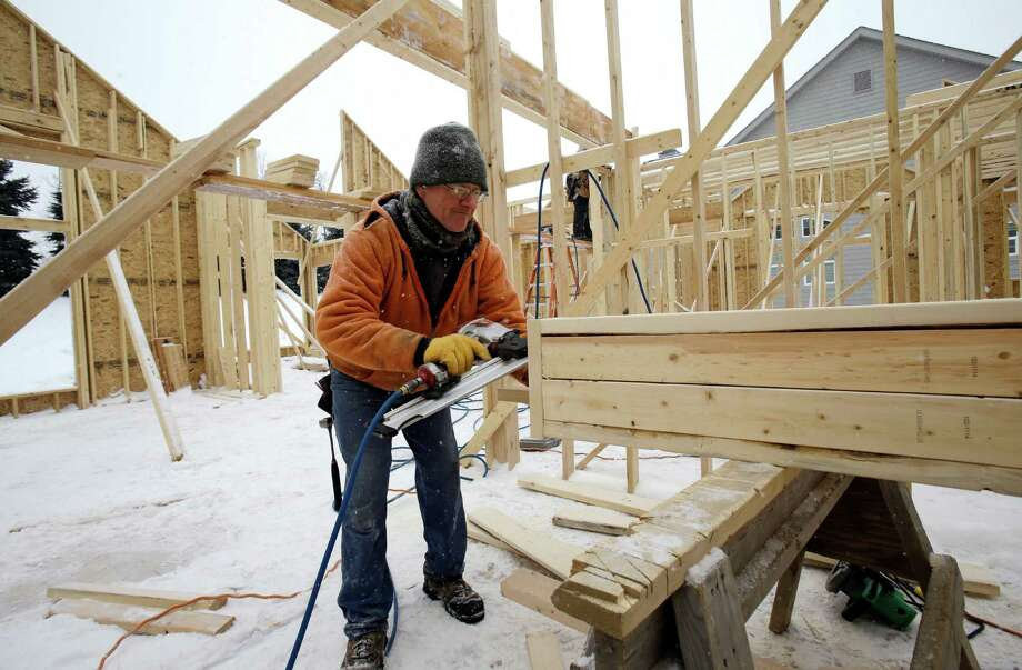 In this Wednesday, Feb. 18, 2015, photo, carpenter Joe Tominc cuts wood for a post on a new construction home in Pepper Pike, Ohio. The Commerce Department issues its last of three estimates of how the U.S. economy performed in the January-March quarter on Wednesday, June 24, 2015. (AP Photo/Tony Dejak) Photo: Tony Dejak, STF / AP