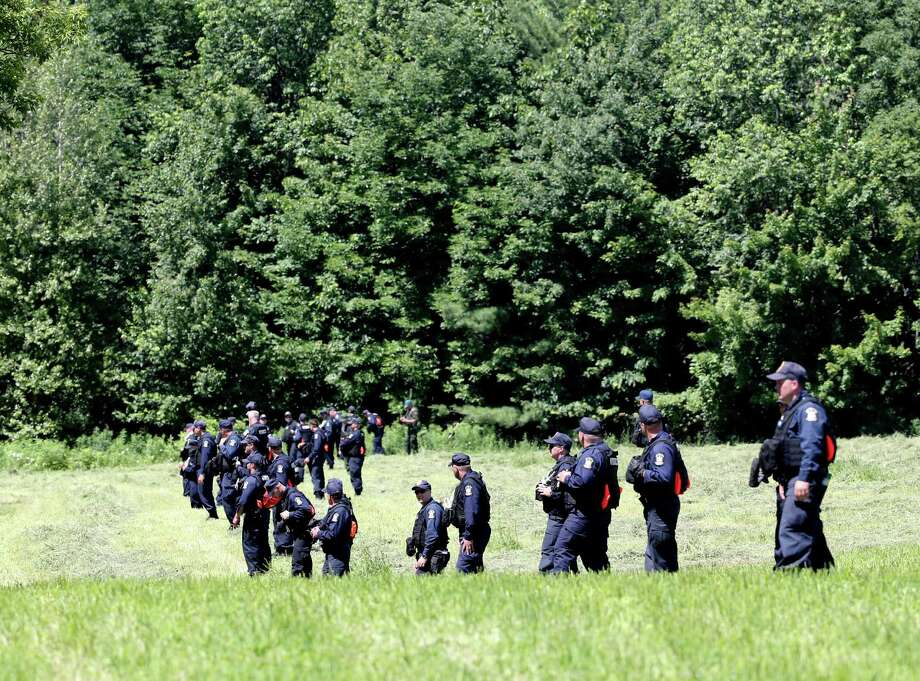 Officers walk through a field in Malone, N.Y., searching for the Clinton Correctional Facility escapees. The search area includes woods so thick that visibility is only a few feet in places. Photo: Mike Groll /Associated Press / AP