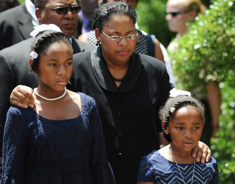 Sen. Clementa Pinckney's wife Jennifer Pinckney, center, and her daughters, Eliana, left, and Malana, right, follow his casket into the South Carolina Statehouse, Wednesday, June 24, 2015, in Columbia, S.C. Pinckney's open coffin was being put on display under the dome where he served the state for nearly 20 years. Pinckney was one of those killed in a mass shooting at the Emanuel AME Church in Charleston. (AP Photo/Rainier Ehrhardt) Photo: Rainier Ehrhardt, FRE / FR155191 AP