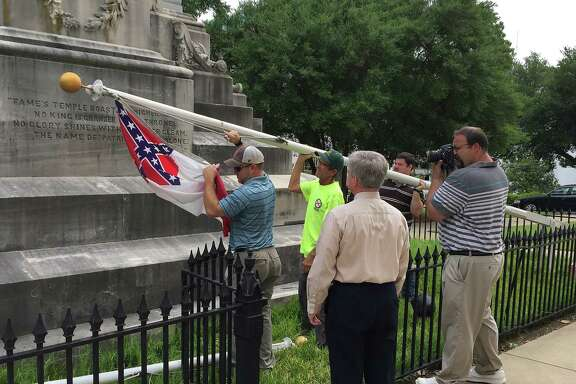 State workers take down a Confederate national flag on the grounds of the state Capitol, Wednesday, June 24, 2015, in Montgomery, Ala. Alabama Gov. Robert Bentley ordered Confederate flags taken down from a monument at the state Capitol. (AP Photo/Martin Swant)
