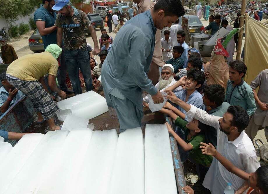 Pakistanis receive ice outside a hospital during heatwave in Karachi on June 24, 2015. Nearly 700 people have died in a severe three-day heatwave in Pakistan, officials said with medics battling to treat patients as a state of emergency was declared in hospitals. AFP PHOTO / RIZWAN TABASSUMRIZWAN TABASSUM/AFP/Getty Images Photo: RIZWAN TABASSUM, Stringer / AFP