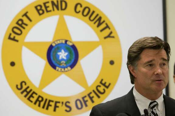 """Fort Bend County District Attorney John Healey speaks during a news conference announcing the results of a large drug bust involving steroids Wednesday, May 27, 2009, in Rosenberg. Several suspects were taken into custody in what was dubbed the largest narcotics investigation in the history of Fort Bend County. The operation called """"Farmacia de Juicy Phruit"""" involves the distribution of thousands of doses of anabolic steroids, human growth hormones, ecstasy an other drugs, law enforcement said in a statement Wednesday. Rodney Clarke, Special Agent-in-Charge, I.R.S. Houston Criminal Investigations, is shown on the right. ( Brett Coomer / Chronicle )"""