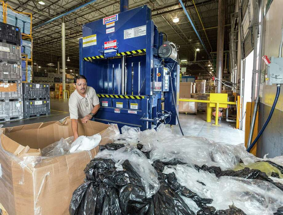 Igloo senior manager Carlos Lopez shows off the machine that compacts the plastic bags for shipping. Photo: Craig Hartley /For The Chronicle / Copyright: Craig H. Hartley