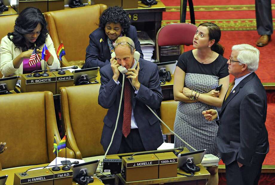 Director of Legislative Operations Brian Coyne has a phone to each ear during voting in the Assembly chamber at the New York State Capitol on Wednesday, June 24, 2015, in Albany, N.Y. Assembly members Nily Rozic and Charles Lavine, right, stand next to him. (Lori Van Buren / Times Union) Photo: Lori Van Buren / 00032380A