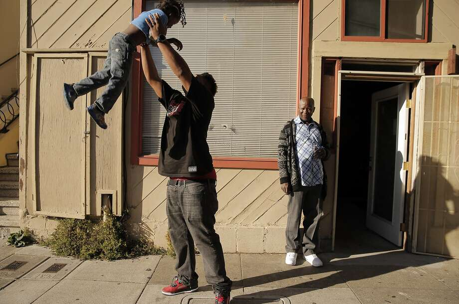 Doug Adams lifts Clarence Williams III up in the air as Clarence's father, Clarence Jr., right, watches in the Bayview Neighborhood of San Francisco, Calif., on Wednesday, June 24, 2015. A new Stanford study shows that black middle class families are much less likely to live in a good neighborhood than their white peers of the exact same income. The researchers calculated average median incomes for neighborhoods and found that blacks and Hispanics at all rungs of the economic ladder came out substantially worse than their white and Asian peers. Photo: Carlos Avila Gonzalez, The Chronicle