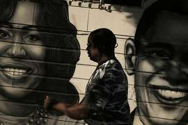 Mario Fisher walks by a mural of President Barack Obama and First Lady Michelle Obama in the Bayview Neighborhood of San Francisco, Calif., on Wednesday, June 24, 2015. A new Stanford study shows that black middle class families are much less likely to live in a good neighborhood than their white peers of the exact same income. The researchers calculated average median incomes for neighborhoods and found that blacks and Hispanics at all rungs of the economic ladder came out substantially worse than their white and Asian peers.