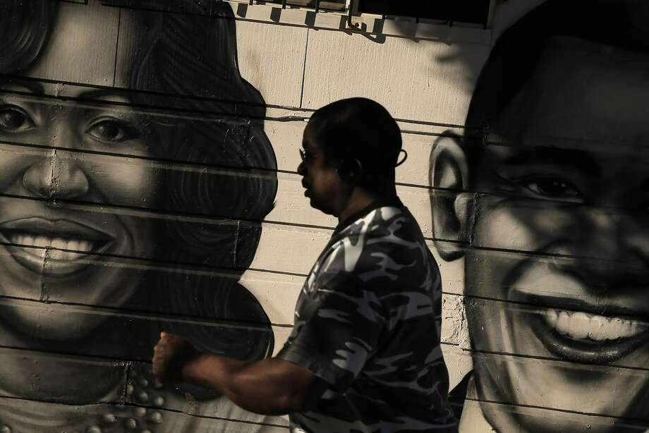 Mario Fisher walks by a mural of President Barack Obama and First Lady Michelle Obama in the Bayview Neighborhood of San Francisco, Calif., on Wednesday, June 24, 2015. A new Stanford study shows that black middle class families are much less likely to live in a good neighborhood than their white peers of the exact same income. The researchers calculated average median incomes for neighborhoods and found that blacks and Hispanics at all rungs of the economic ladder came out substantially worse than their white and Asian peers. Photo: Carlos Avila Gonzalez, The Chronicle