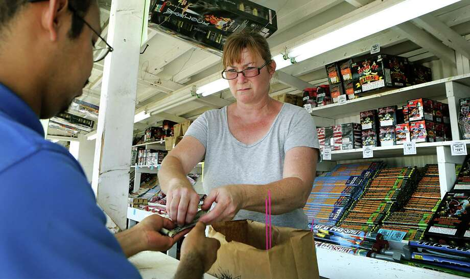 Karen Jurney, a fireworks stand manager, makes a sale at the family stand on Highway 87 near China Grove, on Wednesday, June 24, 2015. It was the first day for fireworks stands to be open. Photo: Bob Owen /San Antonio Express-News / San Antonio Express-News