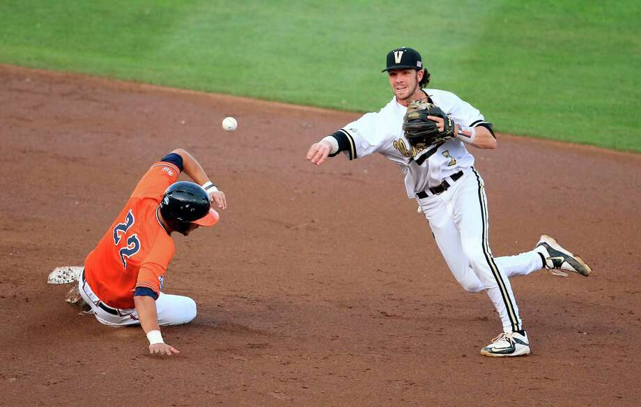 Vanderbilt shortstop Dansby Swanson (7) throws to first base to complete a double play after forcing Virginia's Daniel Pinero (22) at second on a Matt Thaiss grounder during the third inning of Game 3 of the best-of-three NCAA baseball College World Series finals at TD Ameritrade Park in Omaha, Neb., Wednesday, June 24, 2015. (AP Photo/Nati Harnik) Photo: Nati Harnik, STF / AP