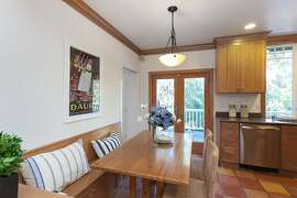 The breakfast nook sits beside French doors opening to a deck and includes a built-in banquette.