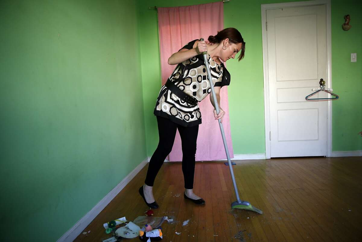 Kelly Dwyer sweeps her daughter's bedroom floor as she prepares to move out of her family's residence in San Francisco, Calif., on Wednesday, June 24, 2015.