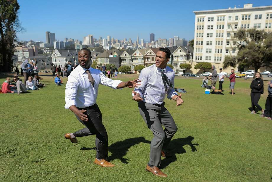 NFL commentators Bart Scott (left) and Tony Gonzalez go deep for a pass while filming a CBS commercial for Super Bowl 50 at Alamo Square Park in San Francisco, California, on Wednesday, June 24, 2015. Photo: Loren Elliott, The Chronicle