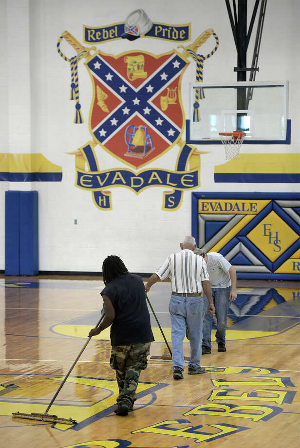 A work crew refinishes the gym floor near the Evadale High School's coat of arms on Wednesday. Due to the recent South Carolina shooting, several states and large companies are reconsidering their use of the Confederate flag.